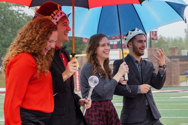 Students in Homecoming Court laugh with their escorts as they walk down the football field.