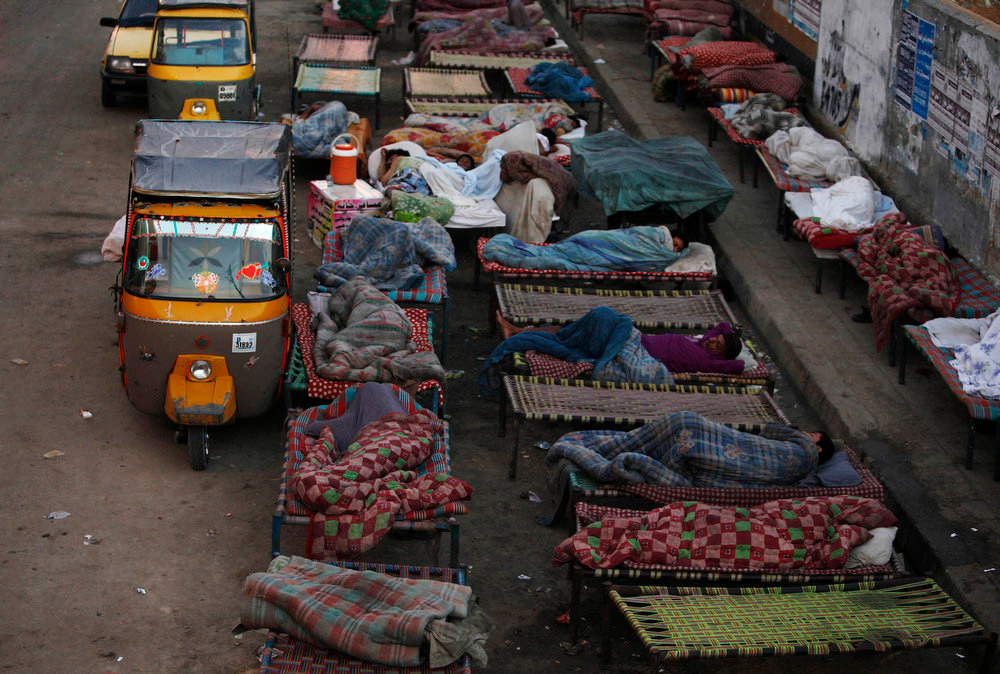 . A general view of men resting on charpoy beds along a road near a railway station in Karachi April 1, 2013. Charpoy bed guesthouses are only set up at night from 9pm to 7am for the homeless, passengers and drivers, charging about 40 Pakistani rupees ($0.40) per night. REUTERS/Akhtar Soomro