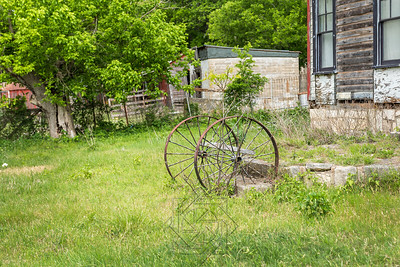Wheels from farm equipment next to abandoned building
