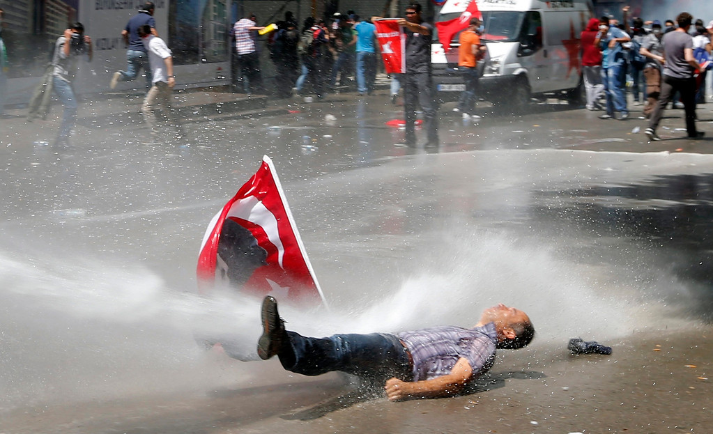 . A man is hit by a jet of water as riot police use a water cannon to disperse demonstrators during a protest against Turkey\'s Prime Minister Tayyip Erdogan and his ruling Justice and Development Party (AKP) in central Ankara June 1, 2013. Erdogan made a defiant call for an end to the fiercest anti-government demonstrations in years on Saturday, as thousands of protesters clashed with riot police in Istanbul and Ankara for a second day.     REUTERS/Umit Bektas