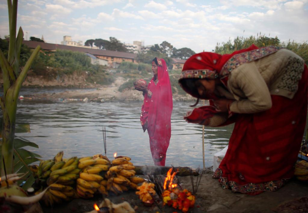 . Nepalese women offer prayers on the banks of the Bagmati River during Chhath puja festival in Katmandu, Nepal, Monday, Nov. 8, 2013.  (AP Photo/Niranjan Shrestha)