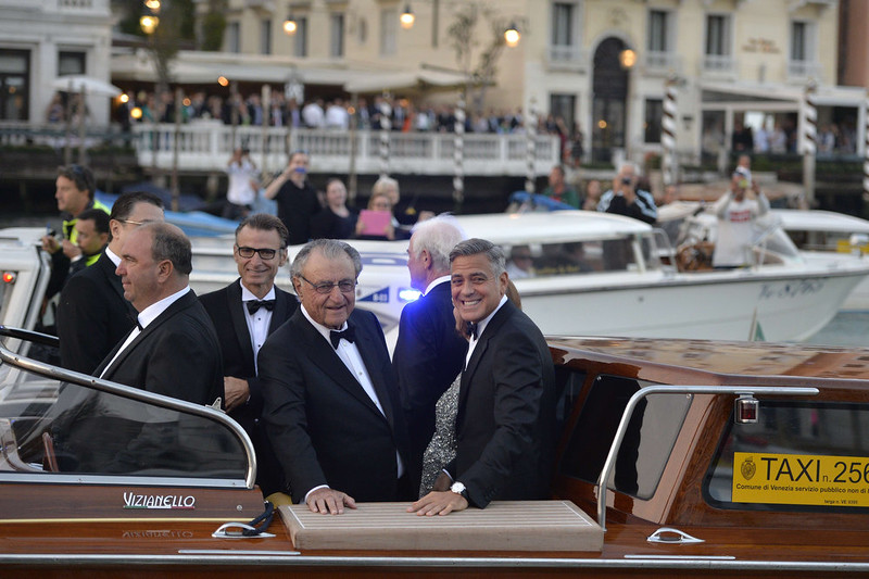 """. US actor George Clooney (R) is pictured on a taxi boat after he leaves the Cipriani hotel on September 27, 2014 in Venice where Clooney and British fiancee, Amal Alamuddin celebrate their wedding. George Clooney has said goodbye to bachelorhood in Venice with a stag party at his favorite restaurant with Hollywood chums, and was gearing up for a day of glamorous pre-wedding celebrations. The actor had swept into the floating city yesterday with his British fiancee Amal Alamuddin on a watertaxi dubbed \""""Amore\"""", zipping up the Grand Canal to cheers from fans at the start of nuptials set to draw out over the weekend.   ANDREAS SOLARO/AFP/Getty Images"""