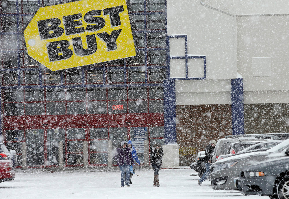 Description of . People walk in the parking lot of a Best Buy store during a severe snow storm in North Olmsted, Ohio Wednesday, Dec. 26, 2012. (AP Photo/Mark Duncan)