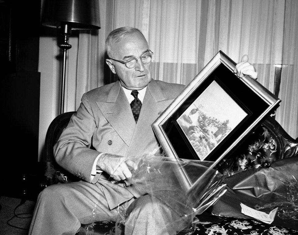 . At his home in Independence, Missouri on Christmas Eve, President Harry S. Truman opens a gift given to him by radio and newspaper correspondents, Dec. 24, 1950. Lifted from the wrappings is a gold framed first engraving of Old Westport Landing on the Missouri River, early settlement from which Kansas City, Missouri developed. (AP Photo/William J. Smith)