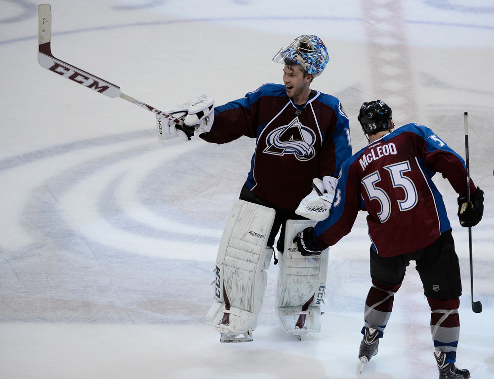 . Colorado Avalanche goalie, Semyon Varlamov, left, points to someone in the stands, celebrating his team\'s victory over the San Jose Sharks at the Pepsi Center Saturday afternoon, March 29, 2014. Teammate, Cody McLeod, who scored a short-handed goal, taps Varlamov on the pads. The Av\'s won 3-2 securing a playoff spot with the win. (Photo By Andy Cross / The Denver Post)