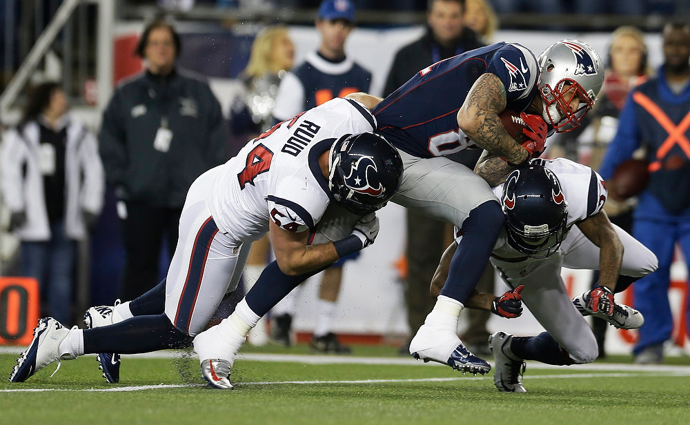 Description of . New England Patriots tight end Aaron Hernandez is tackled by Houston Texans linebacker Barrett Ruud (54) and Johnathan Joseph, right, during the first half of an AFC divisional playoff NFL football game in Foxborough, Mass., Sunday, Jan. 13, 2013. (AP Photo/Elise Amendola)