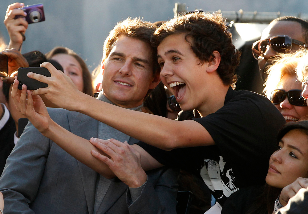 """. Actor Tom Cruise (L) poses with fans along Hollywood Boulevard at the premiere of his new film \""""Oblivion\"""" in Hollywood April 10, 2013.    REUTERS/Fred Prouser"""