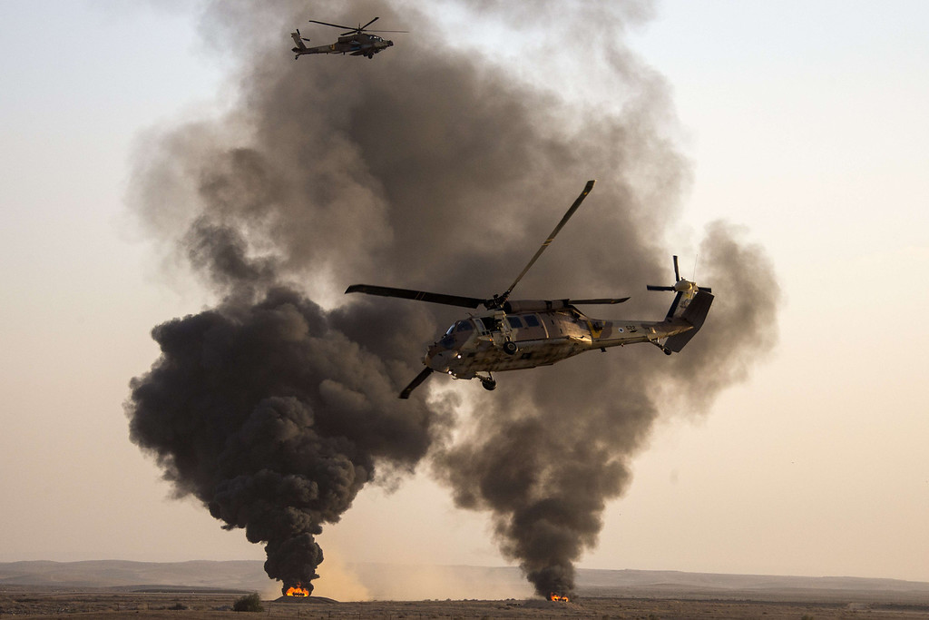 . An Israeli UH-60 Black Hawk (front) and a AH-64 Apache longbow helicopter (back) perform during an air show at the graduation ceremony of Israeli air force pilots at the Hatzerim base in the Negev desert, near the southern Israeli city of Beersheva on December 26, 2013. AFP PHOTO/JACK GUEZ/AFP/Getty Images