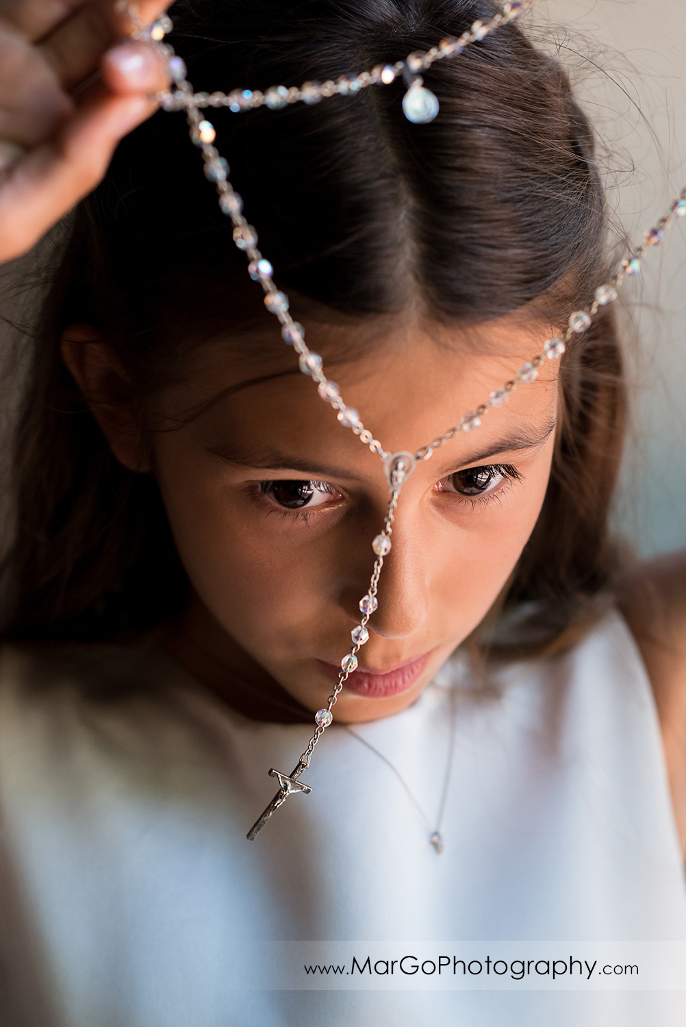 first communion girl in white dress looking through the rosary at Cafe Wisteria in Menlo Park