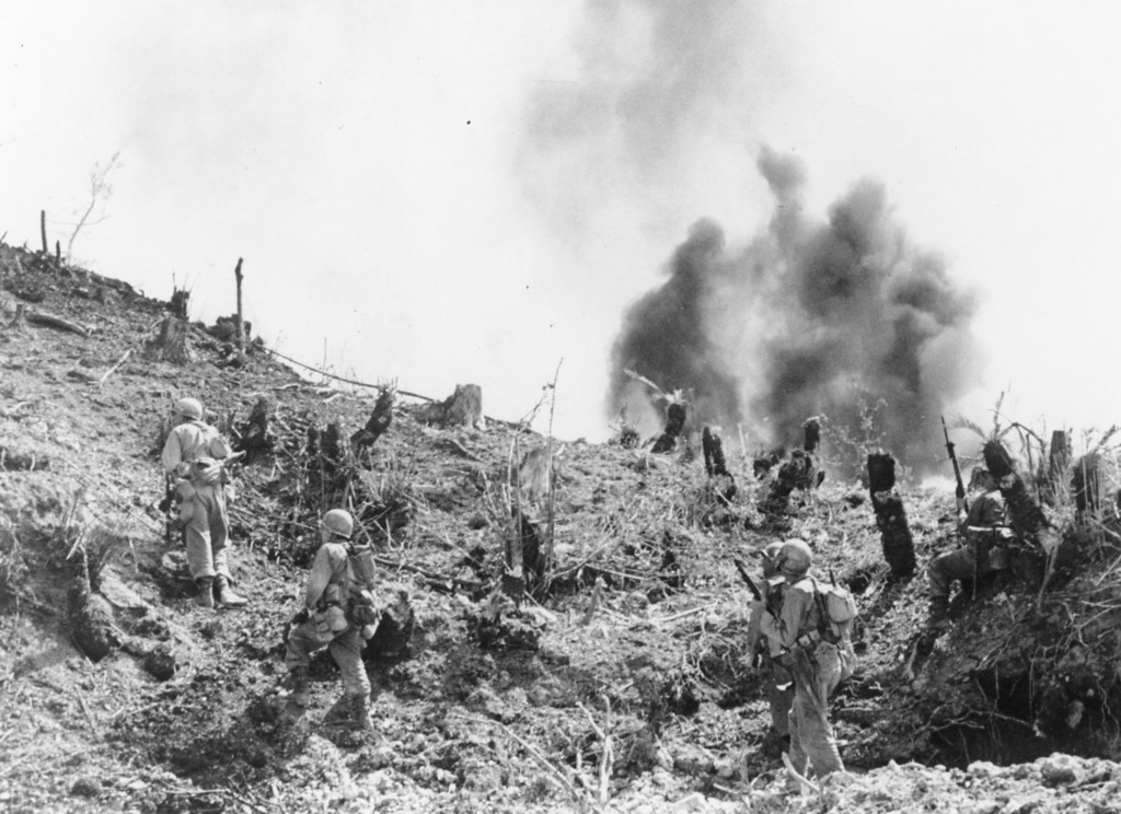 . With Japanese grenades exploding around them, U.S. Marines move up a hill on Skyline Ridge, during the invasion of Okinawa, May 7, 1945. (AP Photo)