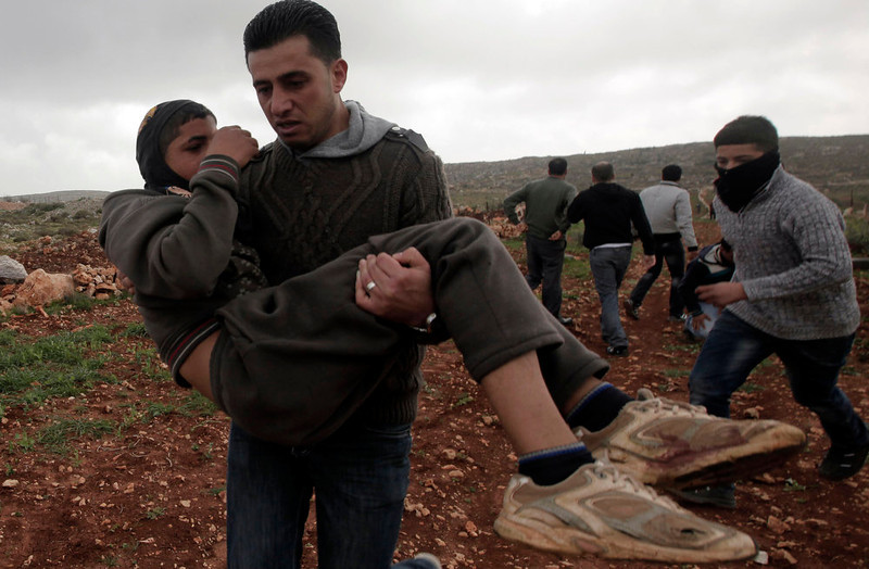 . Palestinians aid a wounded protester following clashes with Israeli settlers in the West Bank village of Qusra near Nablus on February 23, 2013. Three Palestinians were wounded in clashes with Jewish settlers from a wildcat settlement near a village in the northern West Bank, various sources said. JAAFAR ASHTIYEH/AFP/Getty Images