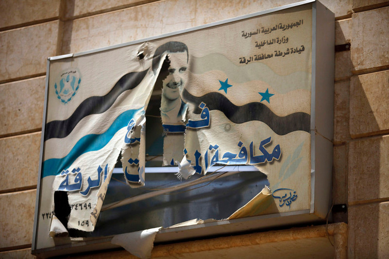 . A torn picture of Syria\'s President Bashar al-Assad is seen on a government building in Raqqa province, east Syria May 8, 2013. REUTERS/Hamid Khatib
