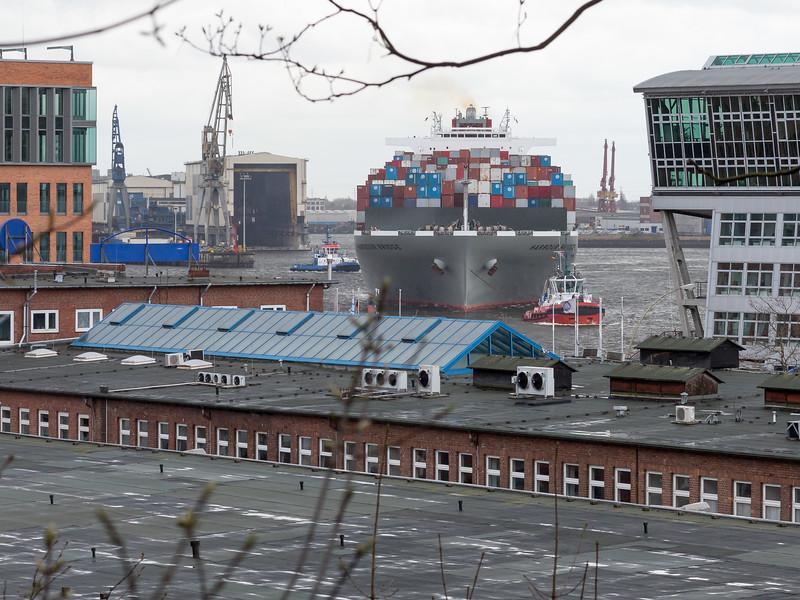 Blick auf Containerschiff im Vorhafen Hamburg mit 2 Schleppern