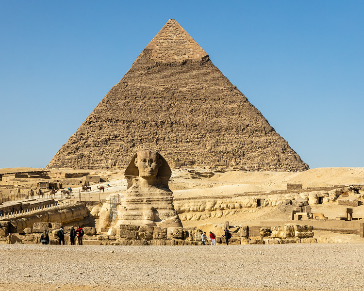 The Sphynx sits in front of a Giza pyramid