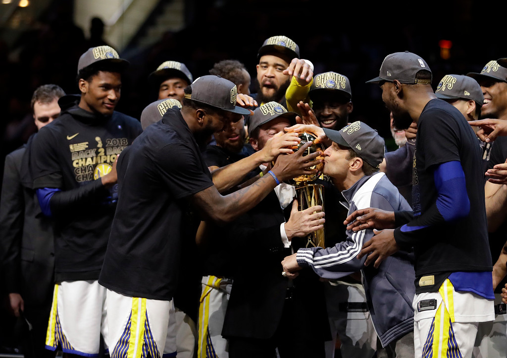 . Golden State Warriors co-owner Peter Guber kisses the trophy after the Warriors defeated the Cleveland Cavaliers 108-85 in Game 4 of basketball\'s NBA Finals to win the NBA championship, Friday, June 8, 2018, in Cleveland. (AP Photo/Tony Dejak)
