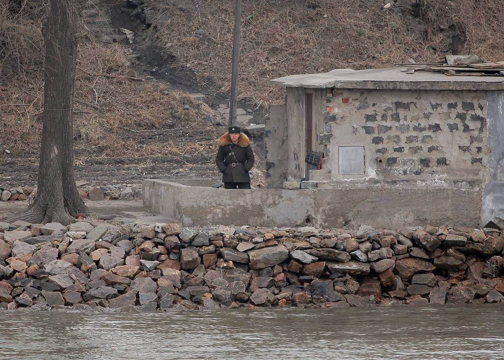 """. A North Korean soldier stands watch by the Yalu River in the North Korean town of Sinuiju across from the Chinese city of Dandong on March 31, 2013. North Korea on March 30 declared it was in a \""""state of war\"""" with South Korea and warned Seoul and Washington that any provocation would swiftly escalate into an all-out nuclear conflict.      CHINA OUT      AFP PHOTO        (Photo credit should read STR/AFP/Getty Images)"""
