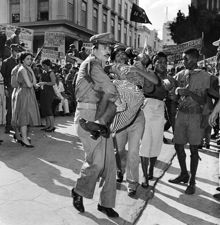 . Rescue workers carry a woman to a first aid station after she fainted in the jam packed mob awaiting appearance of Fidel Castro in front of the Presidential Palace in Havana, Jan. 21, 1959. More than a score fainted in the area near the speakers stand as a hot sun beat down. (AP Photo)