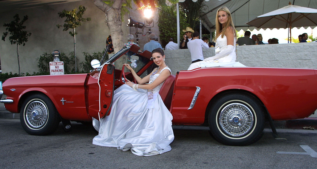 ". Miss Beverly Hills contestants Jennifer MacGregor, left, and Elizabeth Keatinge pose with a1964 Ford Mustang at the opening of ""James Dean - New York 1954,\"" an exhibition of Roy Schatt\'\'s James Dean photographs and benefit party August 4, 2001 at the Edenhurst Gallery in West Hollywood, CA.  (Photo by Nina Prommer/Getty Images)"