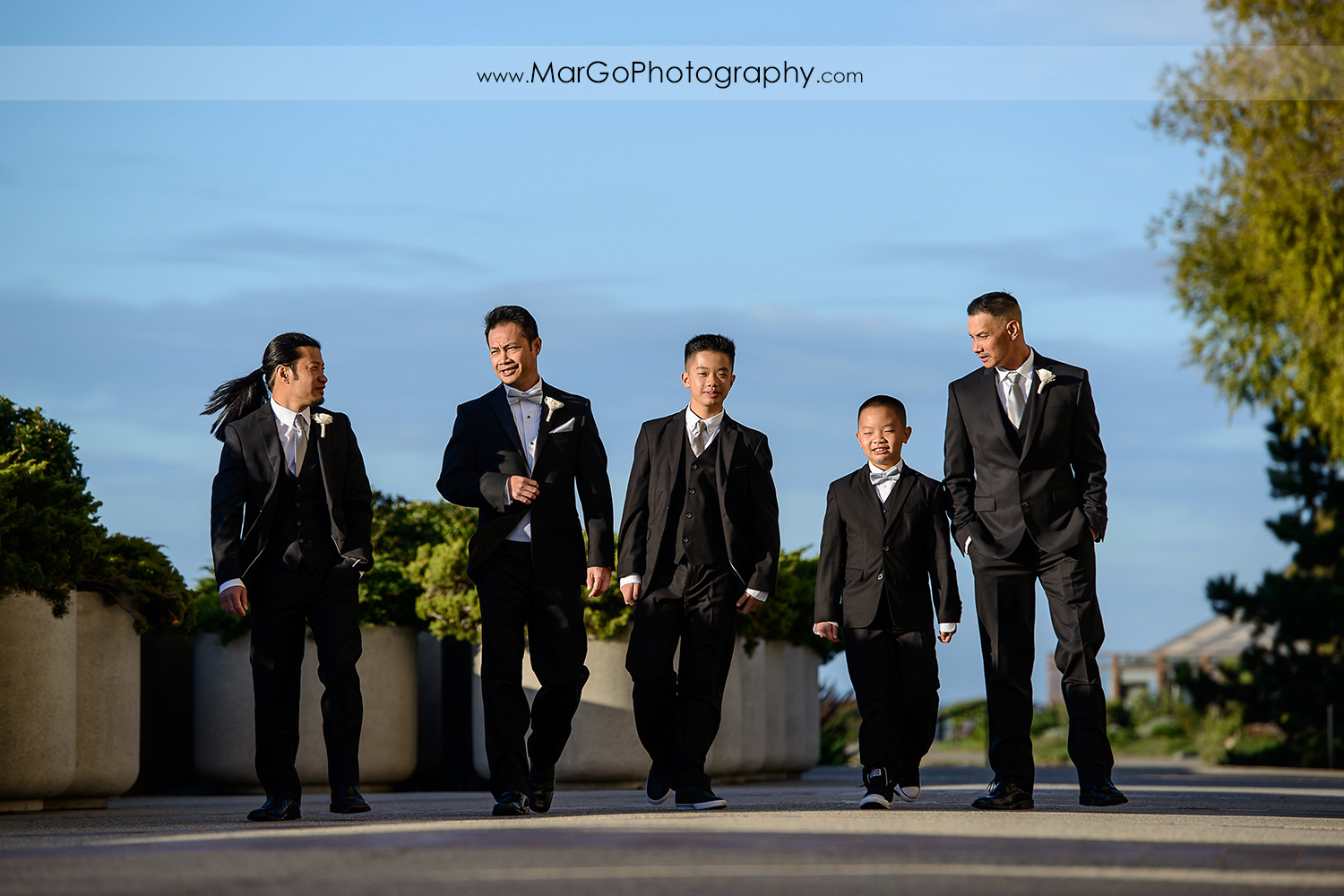 groom and groomsmen walking in front of Hilton San Francisco Airport Bayfront in Burlingame