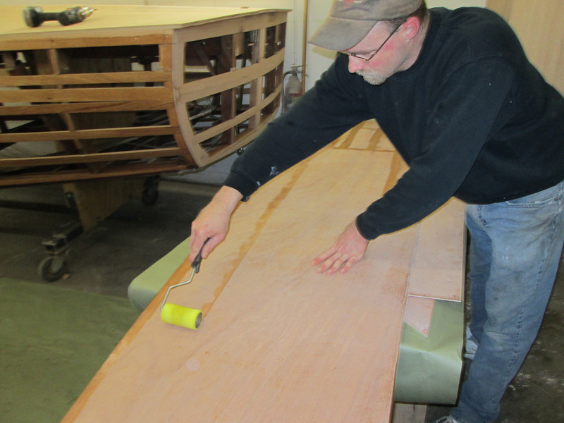 Applying epoxy to the plywood to glue it in place on the side.