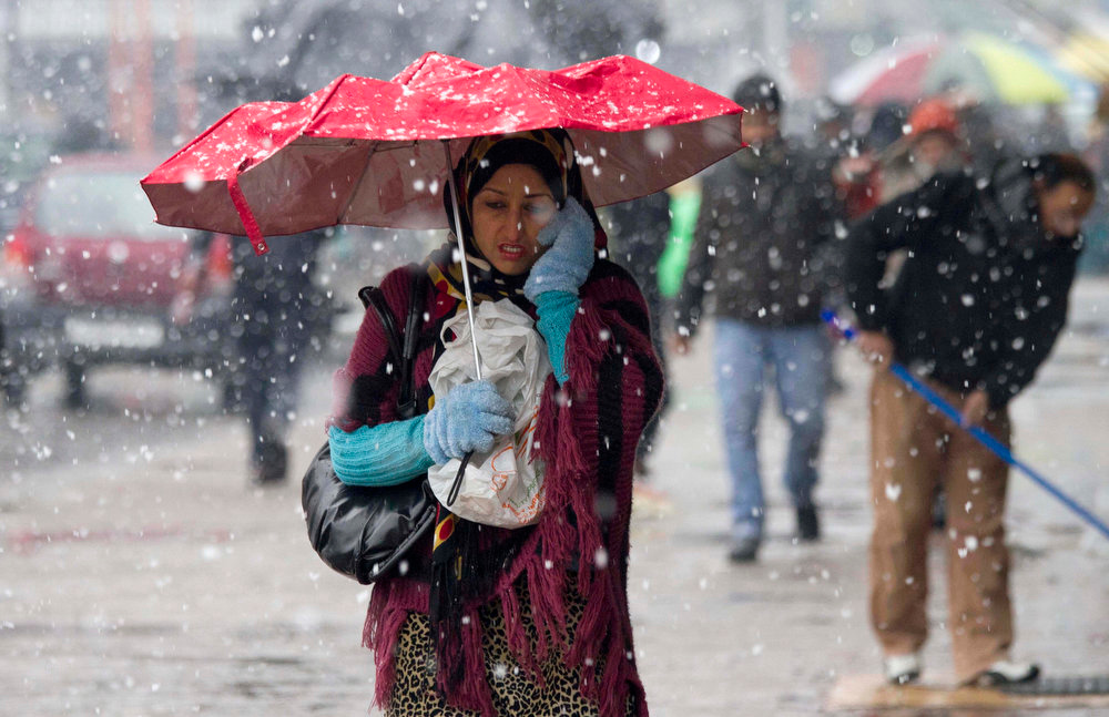 Description of . A Kashmiri woman walks in the snow in Srinagar, India, Saturday, Jan. 12, 2013. Traffic on the 300-kilometer (190-mile) long Jammu-Srinagar national highway was suspended due to heavy snowfall, according to news reports. (AP Photo/ Dar Yasin)