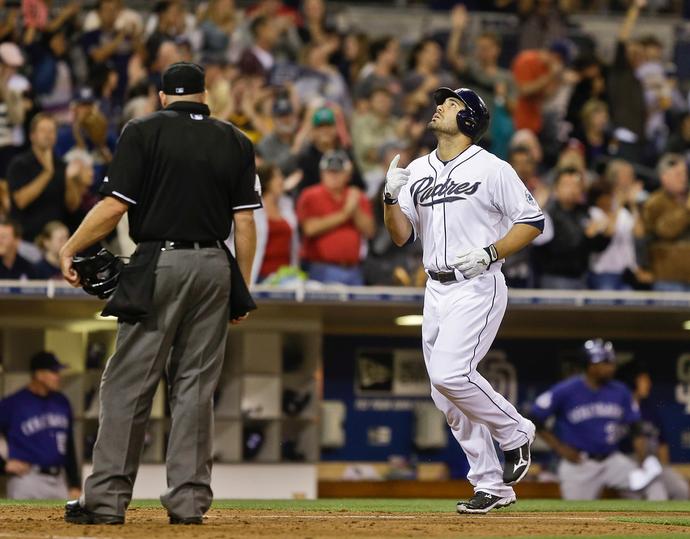 . San Diego Padres\' Carlos Quentin points to the sky as he trots past home plate umpire Ron Kulpa after his two ruin home run against the Colorado Rockies in the sixth inning of a baseball game in San Diego, Wednesday, July 10, 2013. (AP Photo/Lenny Ignelzi)