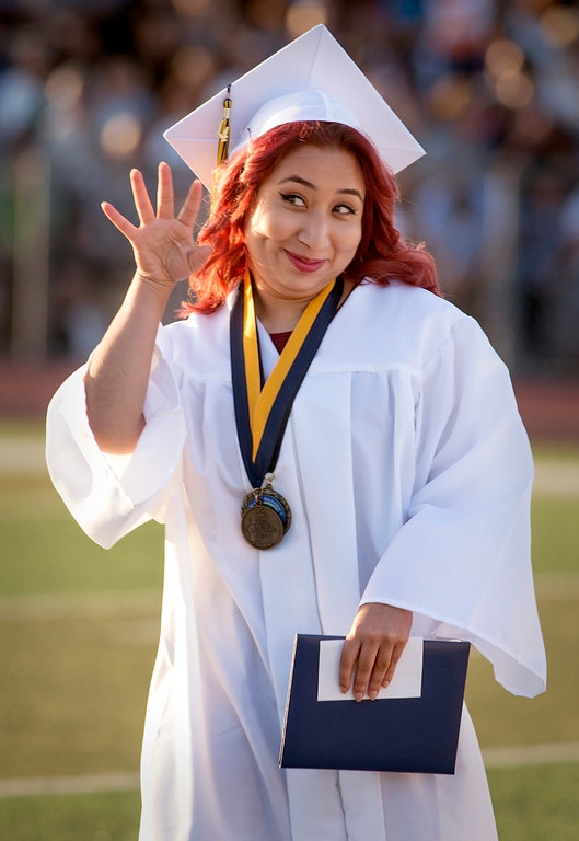 . Montebello High graduate Angelica Yazmin Gutierrez waves to friends and family in the stands during commencement June 19, 2014.  (Staff photo by Leo Jarzomb/Whittier Daily News)