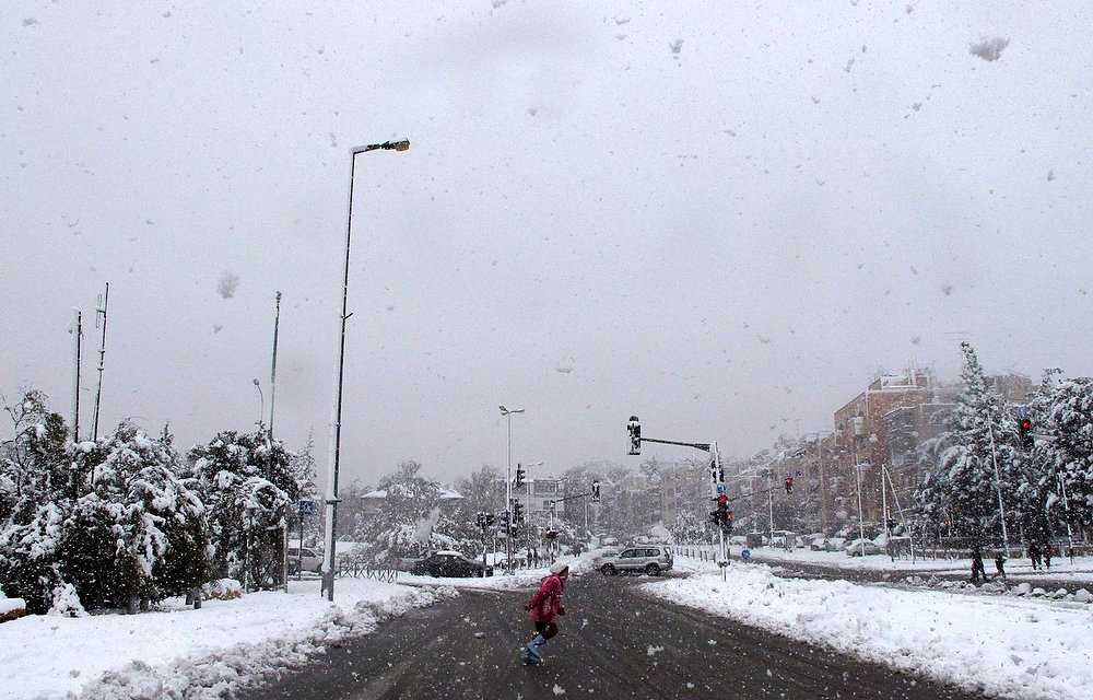Description of . A girl runs across a road during a snowstorm in Jerusalem January 10, 2013. The worst snowstorm in 20 years shut public transport, roads and schools in Jerusalem on Thursday and along the northern Israeli region bordering on Lebanon. REUTERS/Sharon Perry