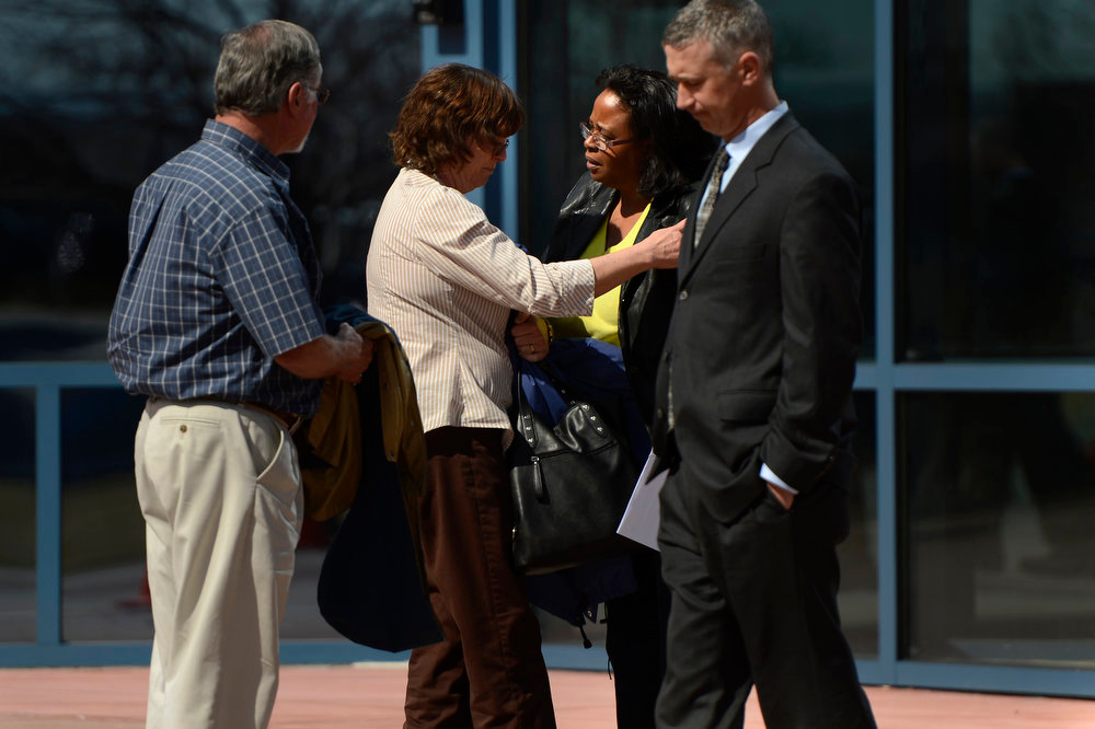 Description of . Arlene Holmes is hugged by Sherry Delaney as she prays in her ear after the James Holmes hearing at the Arapahoe County Justice Center. Delaney and her family rode the elevator down with the Holmes' and her great granddaughter 4 month old Sariah smiled at Arleen Holmes. Delaney said