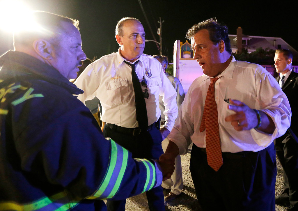 . New Jersey Gov. Chris Christie, right, talks to state fire marshal Bill Kramer, center, and shore regional fire coordinator Craig Augustoni during a visit to the area hit by a massive fire at the Seaside Park boardwalk, Thursday, Sept. 12, 2013, in Seaside Park, N.J. The fire, which apparently started in an ice cream shop and spread several blocks, hit the recently repaired boardwalk, which was damaged last year by Superstorm Sandy. There were no other early reports of any injuries. (AP Photo/Julio Cortez)