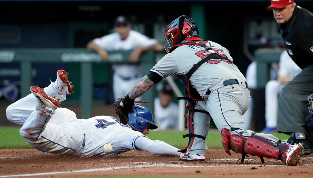 . Kansas City Royals\' Alex Gordon (4) slides and scores next to Cleveland Indians catcher Roberto Perez during the second inning of a baseball game at Kauffman Stadium in Kansas City, Mo., Wednesday, July 4, 2018. (AP Photo/Orlin Wagner)
