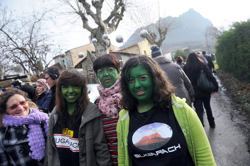 . Women with their faces painted in green walk on December 21, 2012 in the French southwestern village of Bugarach, near the 1,231 meter high peak of Bugarach - one of the few places on Earth some believe will be spared when the world allegedly ends today according to claims regarding the ancient Mayan calendar. French authorities have pleaded with New Age fanatics, sightseers and media crews not to converge on the tiny village.  ERIC CABANIS/AFP/Getty Images