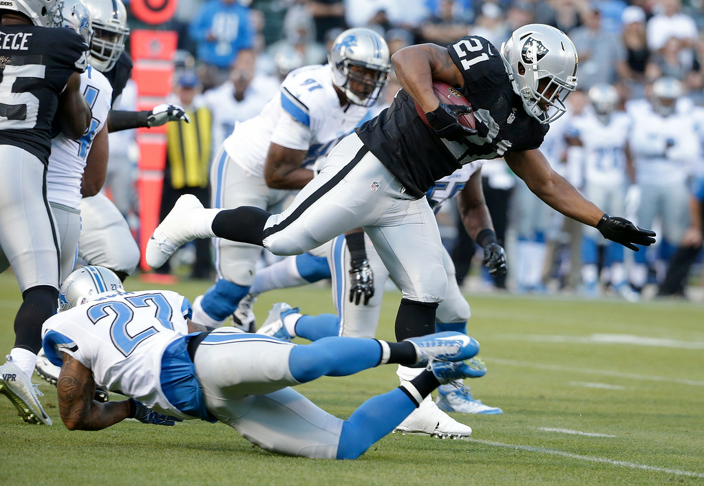 . Oakland Raiders running back Maurice Jones-Drew (21) runs against Detroit Lions strong safety Glover Quin (27) during the first quarter of an NFL preseason football game in Oakland, Calif., Friday, Aug. 15, 2014. (AP Photo/Marcio Jose Sanchez)