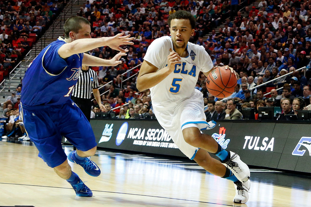 . UCLA forward Kyle Anderson, right, drives with the ball as Tulsa forward Lew Evans defends during the first half of a second-round game in the NCAA men\'s college basketball tournament Friday, March 21, 2014, in San Diego. (AP Photo/Lenny Ignelzi)