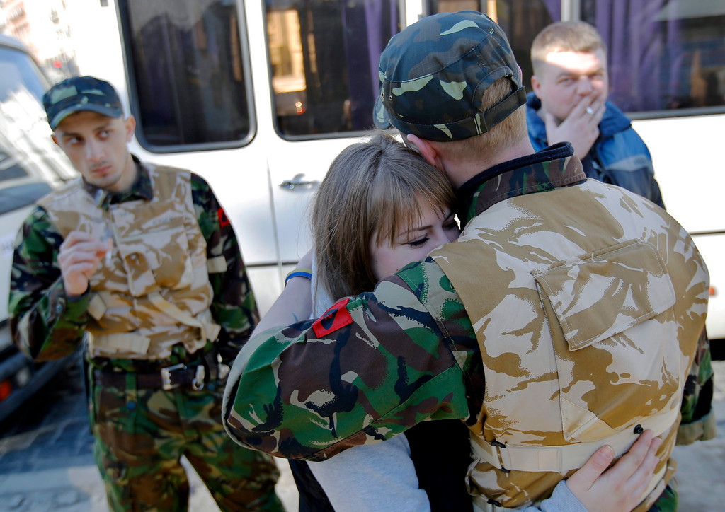 . A young Ukrainian volunteer (R), member of the self defense forces of Maidan, is embraced by his girlfriend before his deployment at a training facility, at the Independence Square in Kiev, Ukraine, 14 March 2014. The volunteers are going to receive proper military training outside Kiev. Ukraine\'s Parliament backed on 13 March the creation of a new National Guard of 60,000 volunteers to supplement its conventional army forces, consisting of 130,000 soldiers. Ukrainian volunteers crowded the recruitment centers in response to the mobilization call, related to the Russian maneuvers in Crimean peninsula. The USA and European Union have threatened sanctions against Moscow over the military standoff in the strategic Crimean peninsula, and are urging Russia to pull back its forces in the region and allow in international observers and human rights monitors. Crimea, which has a majority ethnic Russian population, is strategically important to Russia as the home port of its Black Sea Fleet.  EPA/ROBERT GHEMENT