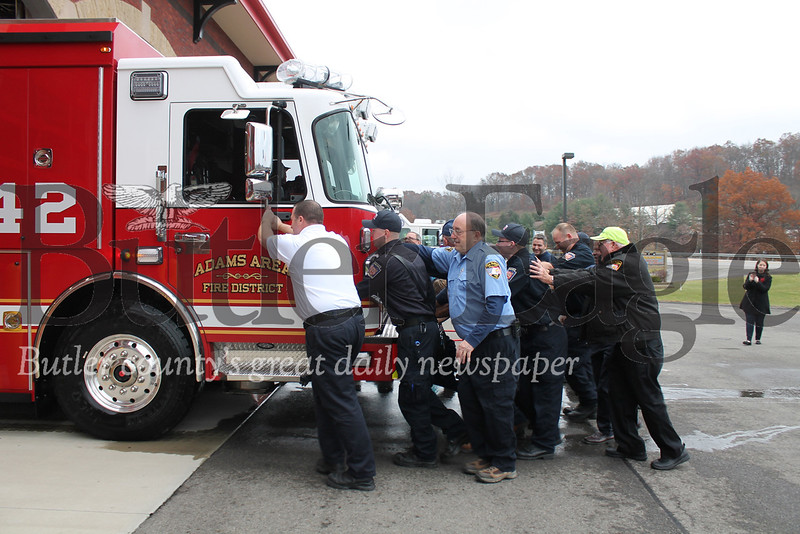 """Members of Adams Area Fire District pushed the new heavy rescue truck into the company garage Sunday. Pushing the truck into place pays tribute to the days when firefighters unhitched horses from the fire wagons before putting equipment away."""