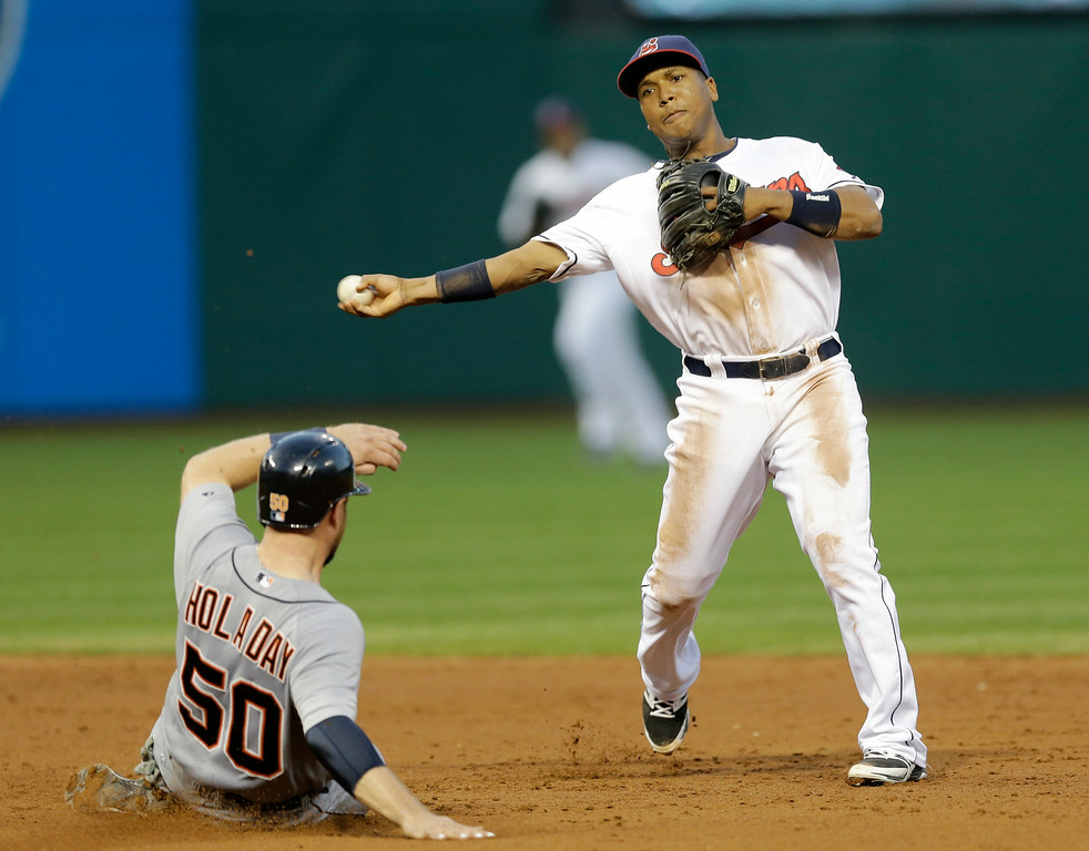 . Cleveland Indians\' Jose Ramirez, right, throws to first base after getting Detroit Tigers\' Bryan Holaday out at second base in the third inning of a baseball game, Wednesday, Sept. 3, 2014, in Cleveland. Ian Kinsler was out at first base for the double play. (AP Photo/Tony Dejak)