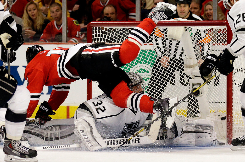 . Chicago Blackhawks\' Jonathan Toews (19)  flies over Los Angeles Kings goalie Jonathan Quick (32) during the second period in Game 1 of the Western Conference finals in the NHL hockey Stanley Cup playoffs in Chicago on Sunday, May 18, 2014. The Blackhawks won 3-1. (AP Photo/Nam Y. Huh)