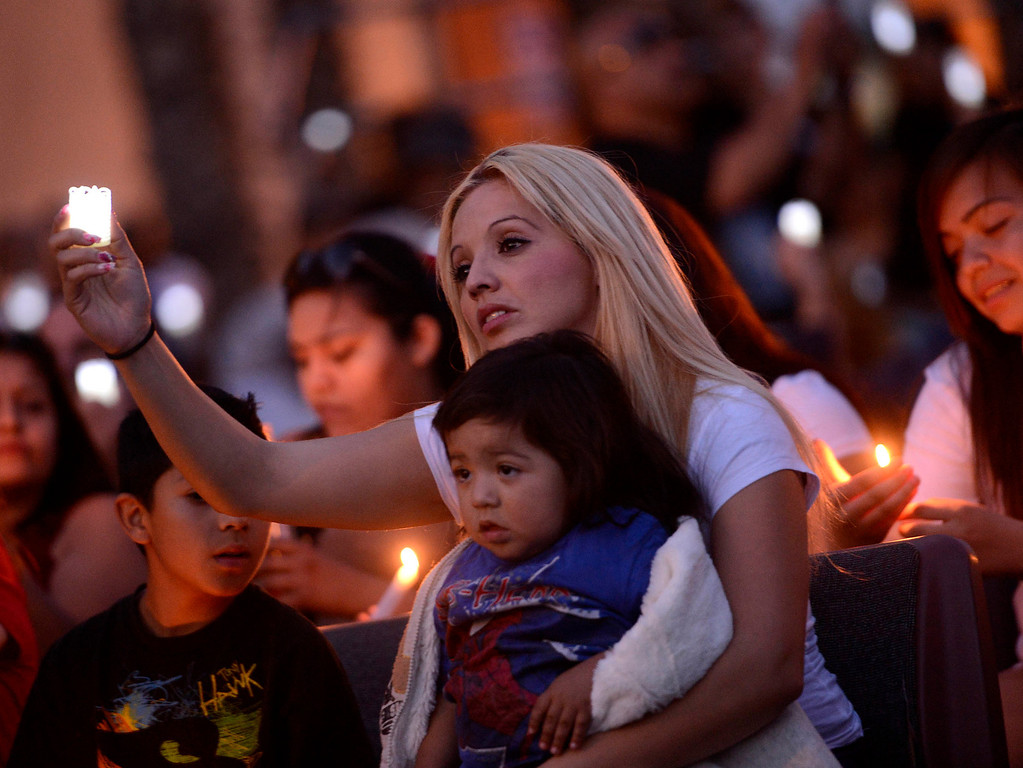 . Alma Espinoza with son Isaac, 1, commemorate the life of her nephew Robert Elizarraraz during the annual Victims Candlelight Vigil at the police station in San Bernardino April 23, 2013.    Elizarraraz died February of 2012 as a victim of violence.  (Photo by Gabriel Luis Acosta/The Sun)