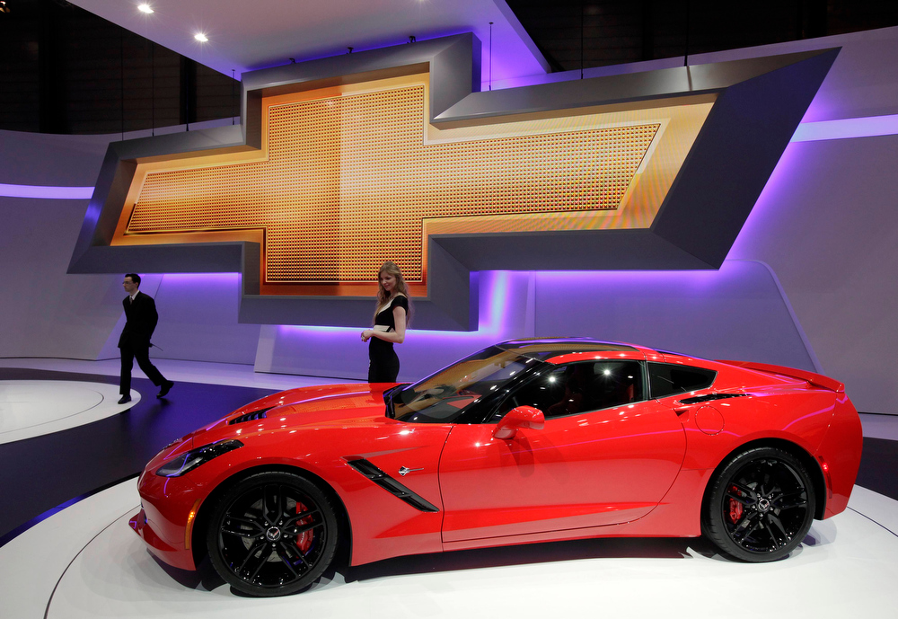. A model stands next to a Corvette car on the Chevrolet booth during the second media day of the 83rd Geneva Car Show at the Palexpo Arena in Geneva March 6, 2013. The Geneva Motor Show will take place from March 7 to 17, 2013. REUTERS/Denis Balibouse