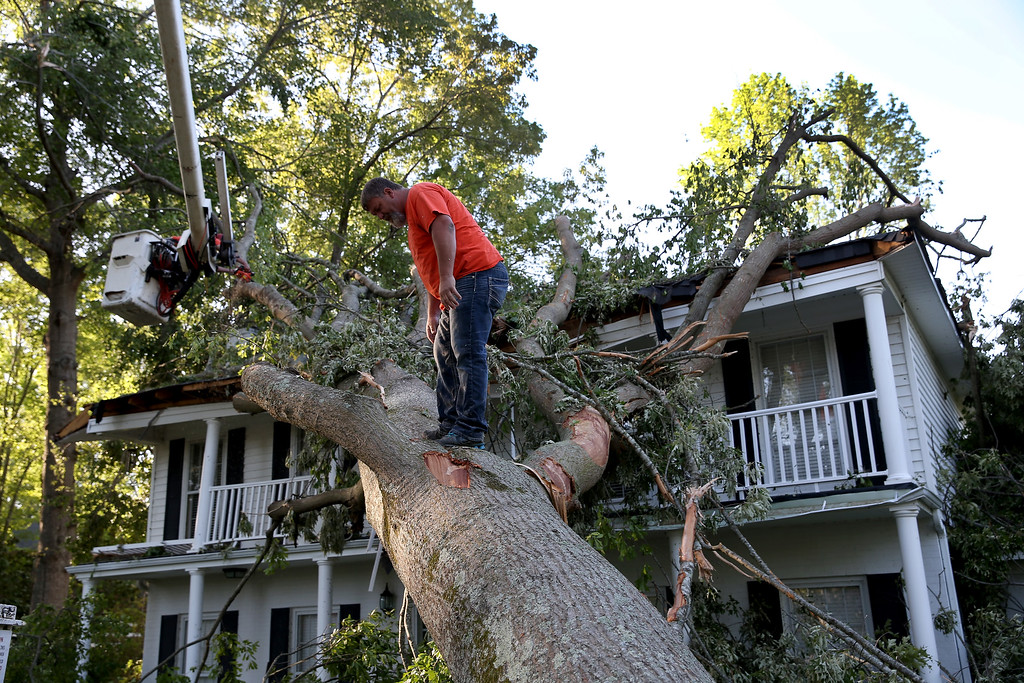 . Rodney Stanford from Brewer Tree Service works on removing a tree that is resting on a home after a tornado struck on Monday, on April 30, 2014 in Tupelo, Mississippi.  Deadly tornadoes ripped through the region over the last few days, leaving more than a dozen dead.  (Photo by Joe Raedle/Getty Images)