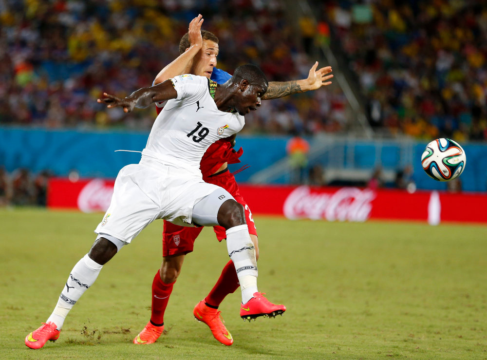 Description of . Ghana's Jonathan Mensah, right, pushes off United States' Fabian Johnson during the group G World Cup soccer match between Ghana and the United States at the Arena das Dunas in Natal, Brazil, Monday, June 16, 2014. (AP Photo/Julio Cortez)