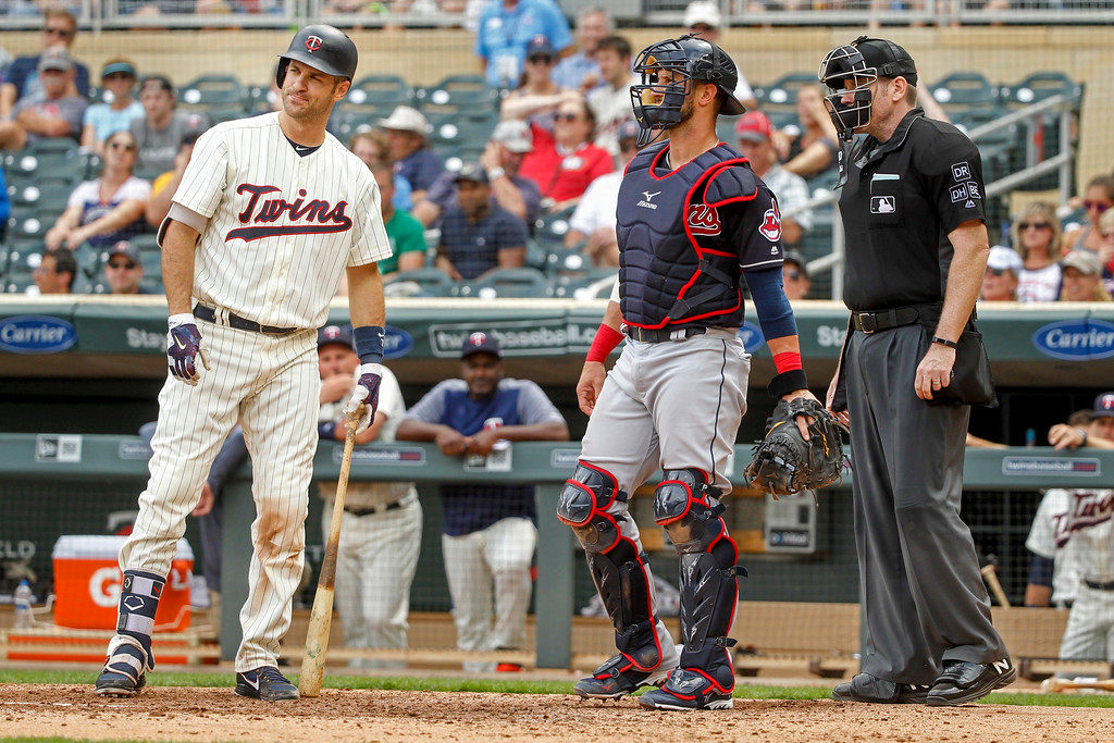 . Minnesota Twins\' Joe Mauer, left, expresses disappointment in the third strike call by umpire Chris Conroy as Cleveland Indians catcher Yan Gomes awaits the next batter in the ninth inning of a baseball game Wednesday, Aug. 1, 2018, in Minneapolis. The Indians won 2-0. (AP Photo/Bruce Kluckhohn)