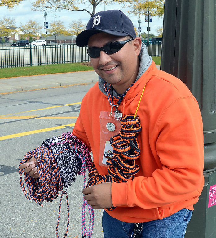 . This street vendor is hoping to sell lots of Tigers necklaces and bracelets at Comerica Park before the start of Game 3 of the ALDS between the Tigers and Oakland A\'s, Monday October 7, 2013. (Oakland Press Photo:Vaughn Gurganian)