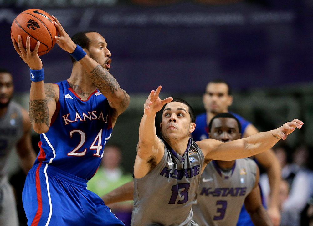 . Kansas guard Travis Releford (24) looks for a teammate to pass to as he is pressured by Kansas State guard Angel Rodriguez (13) during the second half of an NCAA college basketball game Tuesday, Jan. 22, 2013, in Manhattan, Kan. Kansas won 59-55. (AP Photo/Charlie Riedel)