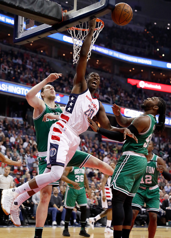 . Washington Wizards center Ian Mahinmi (28) is fouled as he tries to shoot by Boston Celtics center Kelly Olynyk (41) with Celtics forward Jae Crowder (99) nearby, during the first half of Game 6 of an NBA basketball second-round playoff series, Friday, May 12, 2017, in Washington. (AP Photo/Alex Brandon)