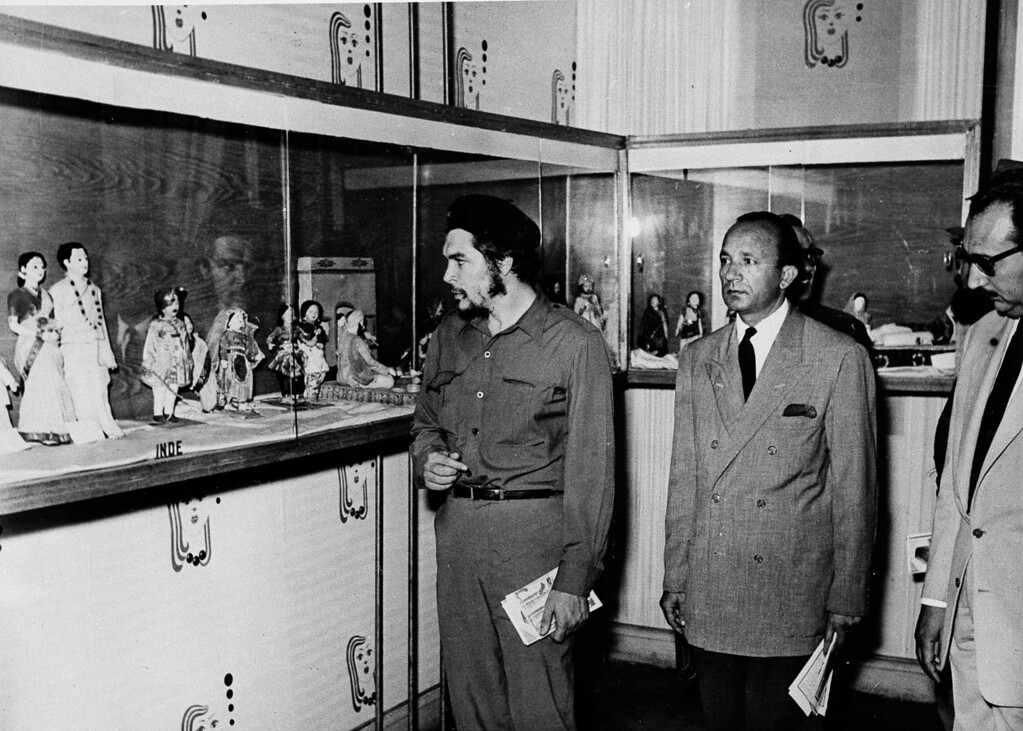 ". Commander Ernesto ""Che\"" Guevara, Cuban President Fidel Castro\'s right hand man, looks at the permanent doll exhibition at Ras-El-Tin Palace, Alexandria, Egypt, June 20, 1959.  At center is Alexandria\'s Governor Ismail Mehanna.  Man at far right is unidentified.  (AP Photo/Abdel Latif)"