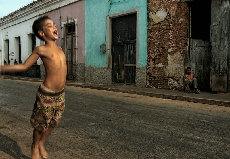With constant political pressure from the outside world, Cuba is still a sworn communist state. A young boy with an uncertain future jumps up as if to shout for freedom. An older, more experienced man observes passively from a distance.   Remedios, Cuba, 2006.