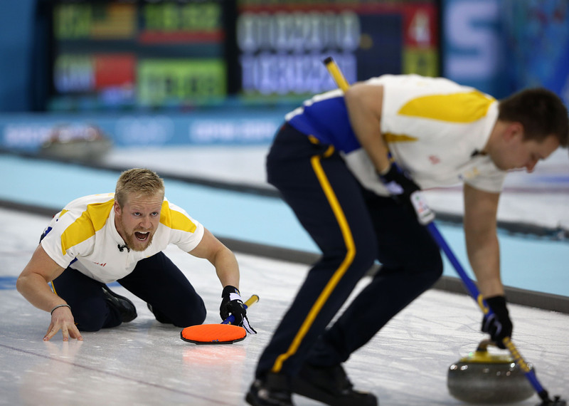 . Sweden\'s Niklas Edin (L) reacts after throwing his stone during the men\'s curling round robin session 3 match between Sweden and Canada at the Ice Cube curling centre in Sochi on February 11, 2014 during the 2014 Sochi winter Olympics. (ADRIAN DENNIS/AFP/Getty Images)