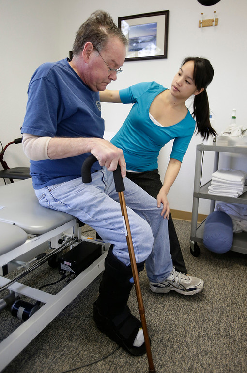 . Gary Richards builds his strength to stand up with the help of physical therapist, Lisa Yee, during a physical therapy session for a heel problem in Cupertino, Calif. on Thursday, Feb. 28, 2013. Richards  is the Mercury News Roadshow columnist who is calling attention to aging motorists and the issues they face. (Gary Reyes/ Staff)